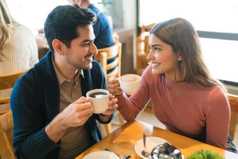 De jeunes amoureux prennent un café en se regardant dans un café