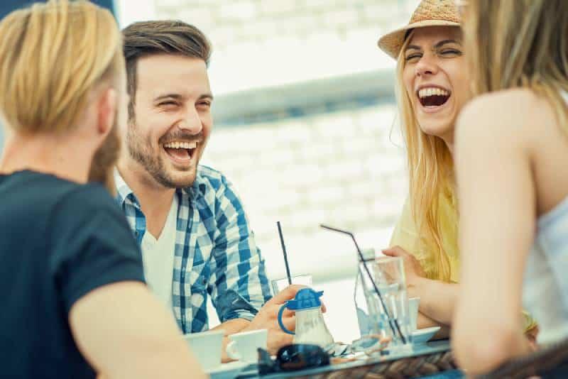 Des amis sourient et s'assoient dans un café, boivent un café et s'amusent ensemble
