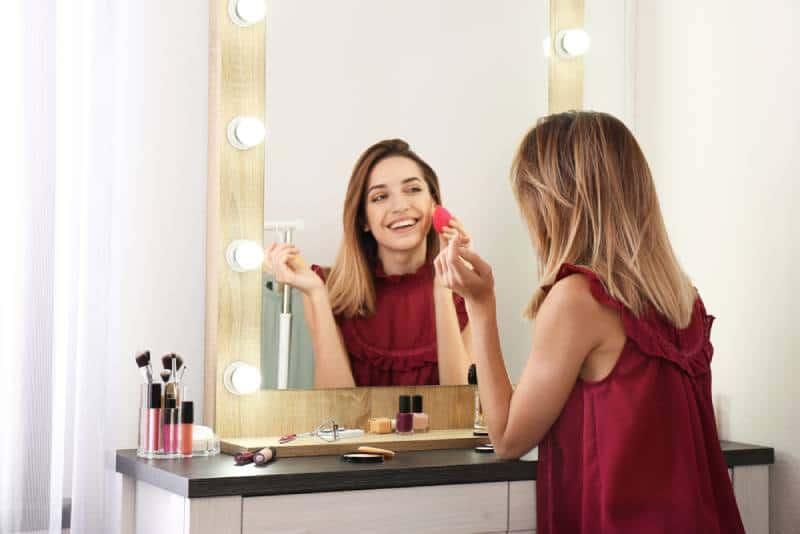 Femme souriante se maquillant devant le miroir