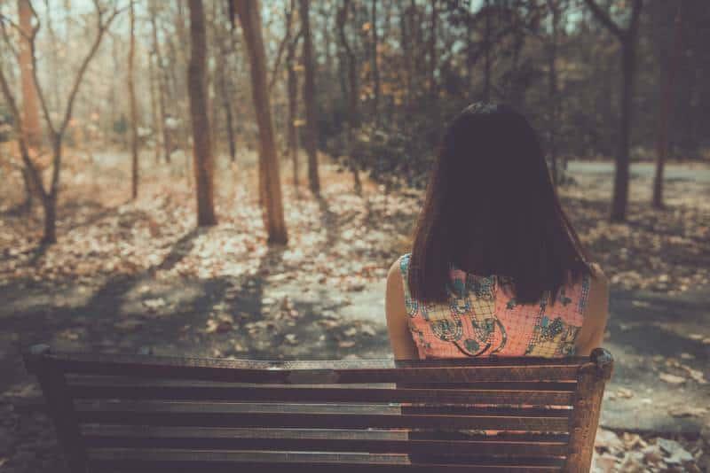 Femme triste assise sur le banc de l'angle du dos dans le parc