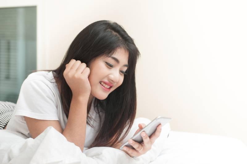 Mme Smile utilise le smartphone et s'allonge sur le lit à la maison
