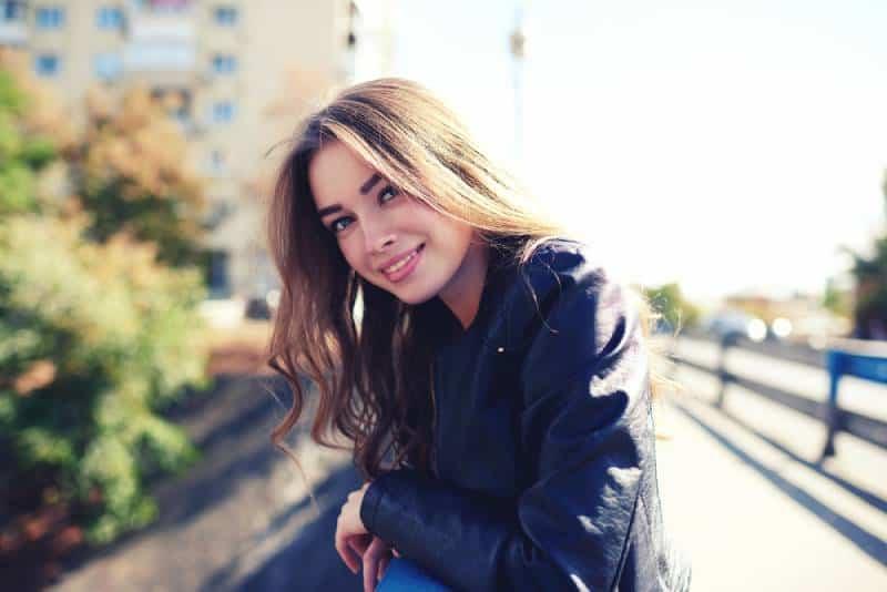 Portrait d'une femme heureuse et souriante, debout sur la place
