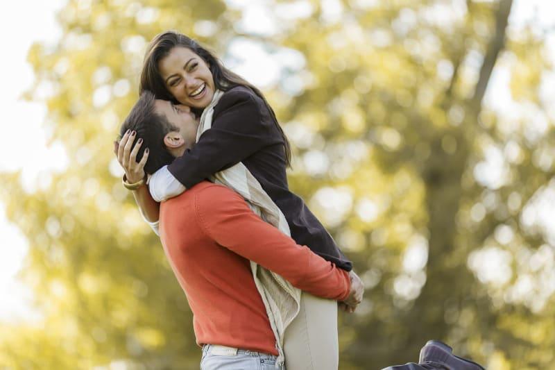 Un couple joyeux s'embrassant dehors dans la nature