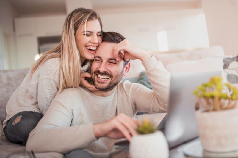 Un couple souriant assis à la maison