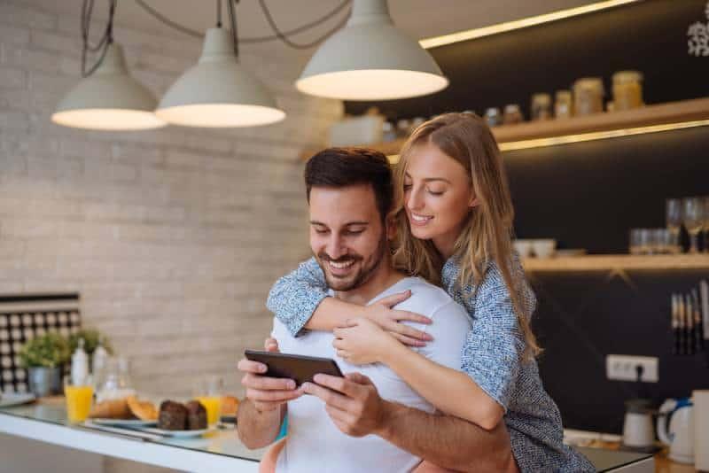 Un couple souriant regarde le téléphone dans la cuisine