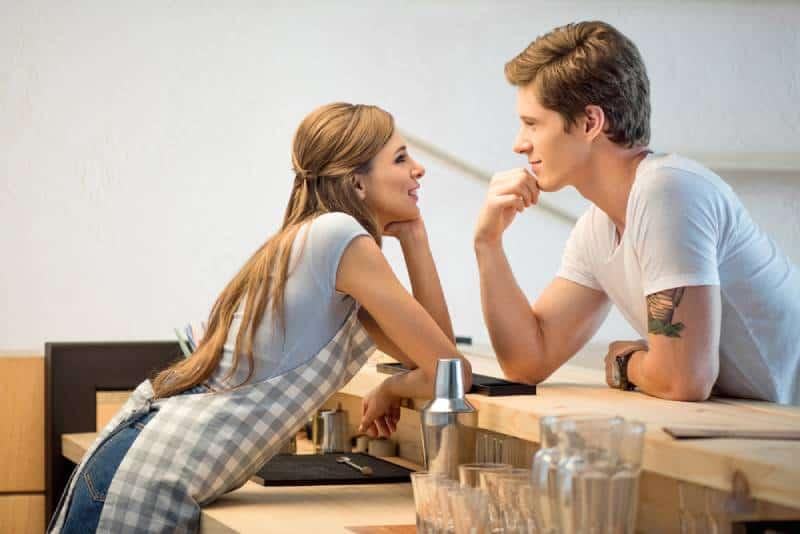 Un homme et une femme flirtent en travaillant dans un café