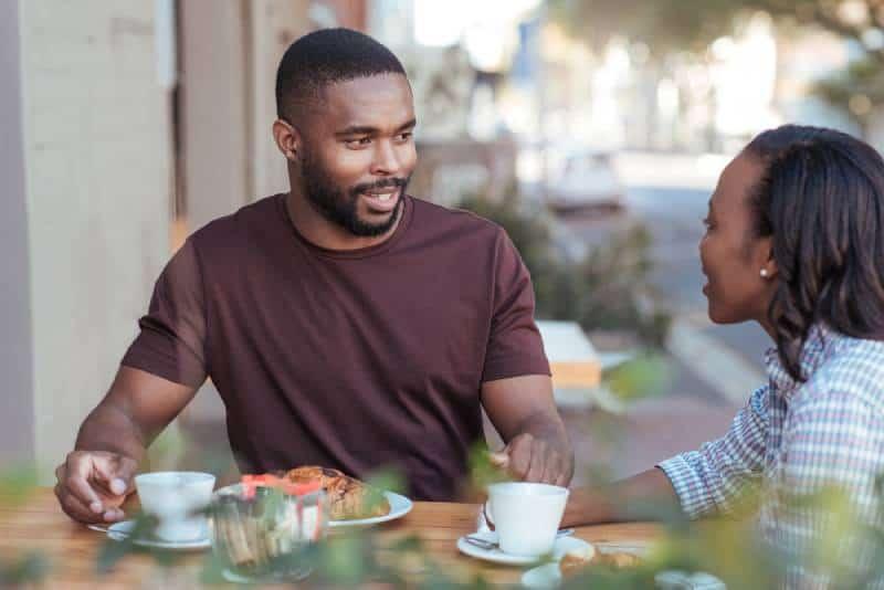 Un jeune couple africain souriant assis à une table dans un café et buvant du café