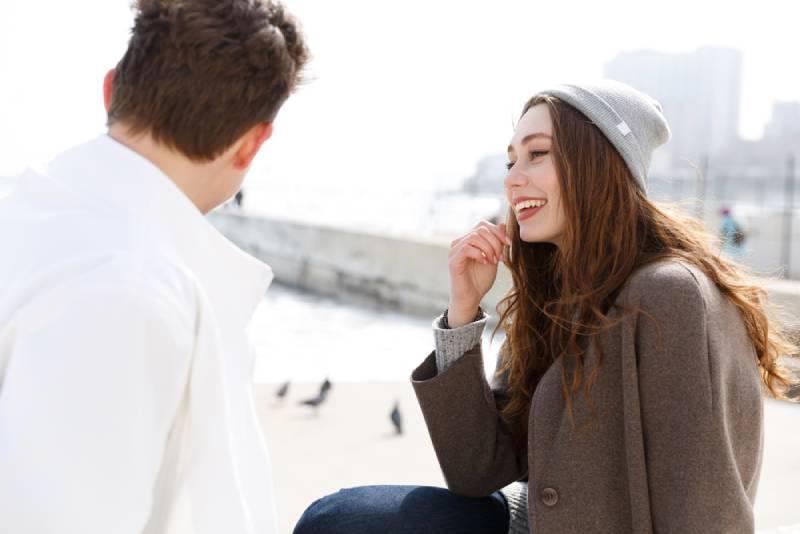 Un jeune couple souriant assis et discutant dehors