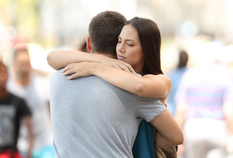Une femme inquiète étreint son petit ami à l'extérieur