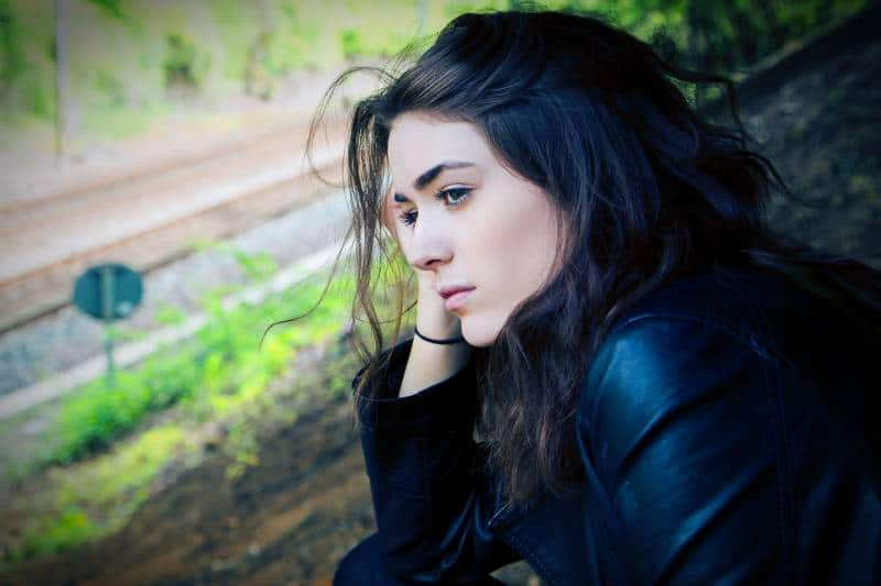 Une femme inquiète, assise dehors dans la nature