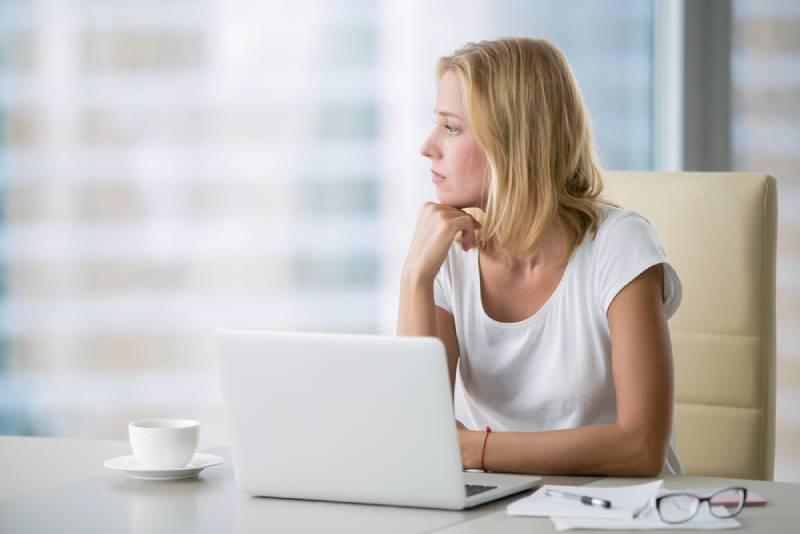 Une femme réfléchie au bureau qui regarde à l'extérieur