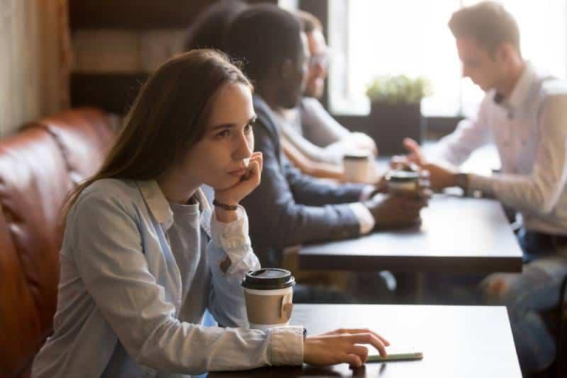 Une fille bouleversée assise au café