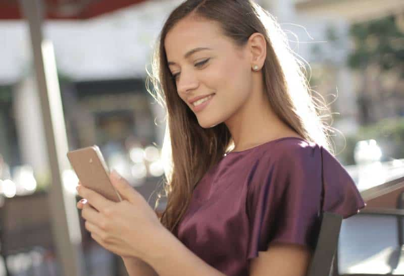Une fille souriante tape au téléphone dans un café