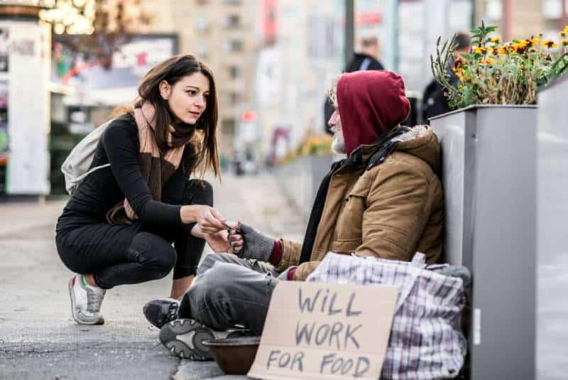 Une jeune femme donne de l'argent à un mendiant sans abri assis en ville