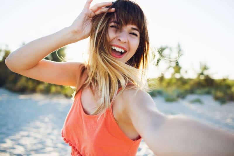 Une jeune femme heureuse s'offre un selfie sur la plage