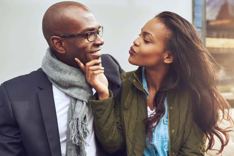 Une jeune fille flirtant avec un homme touche son visage