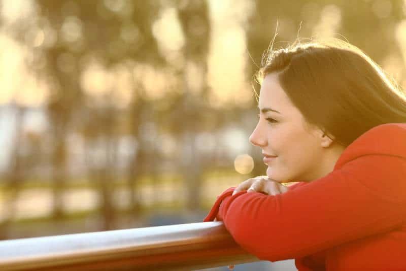 Une jeune fille qui se détend en regardant le coucher de soleil à l'extérieur