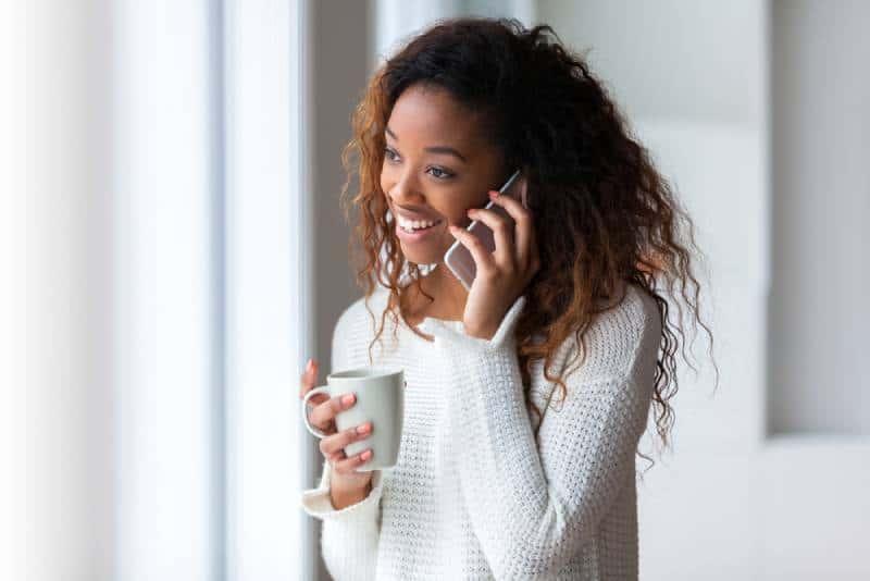 Une jeune fille souriante qui parle au téléphone