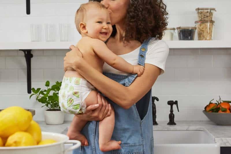 Une mère qui tient son bébé dans ses bras à la cuisine