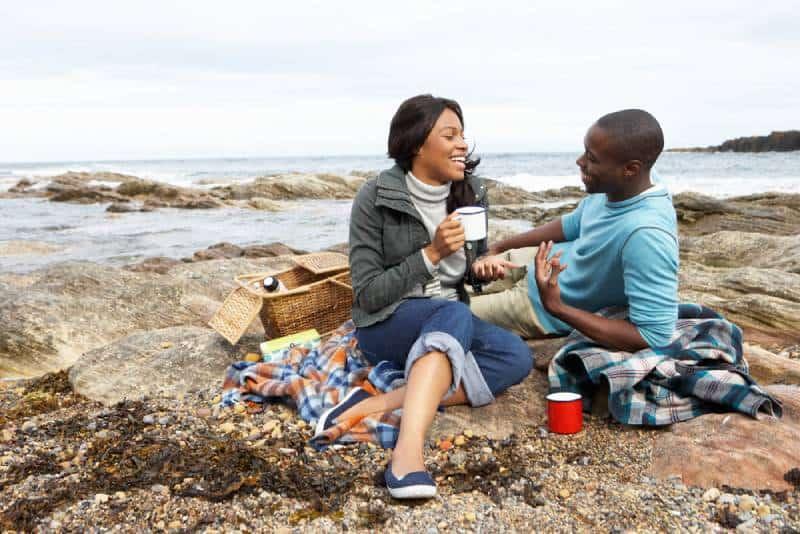 couple assis au bord du lac et discutant