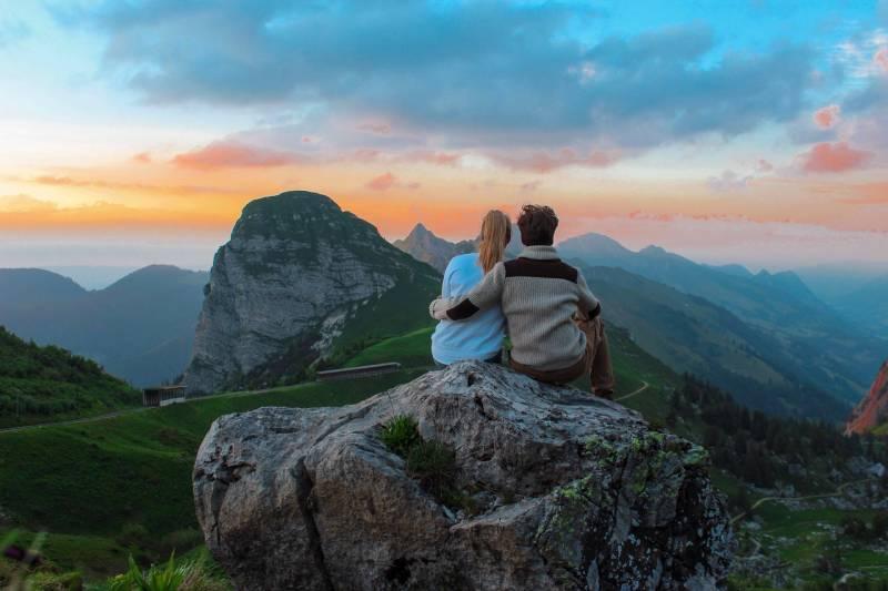 couple assis au sommet d'une colline