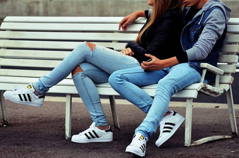 couple assis sur un banc blanc à l'extérieur