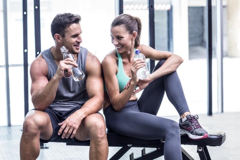 couple buvant de l'eau et s'asseyant au gymnase