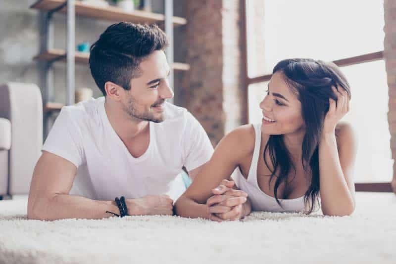 couple romantique allongé sur le tapis douillet de la maison