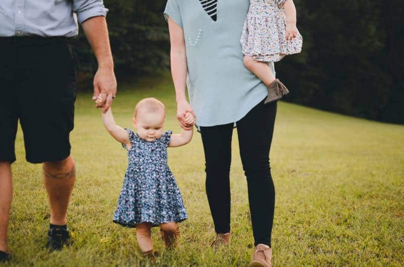 couple tenant le bras de bébé et marchant sur l'herbe