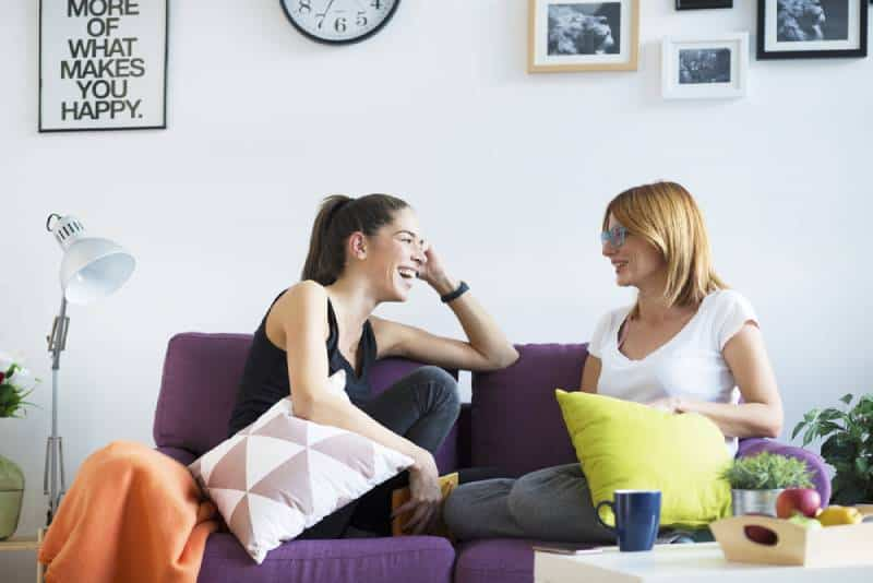 des amies heureuses qui parlent dans le salon
