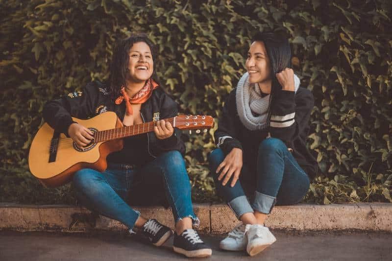 des amis jouent de la guitare sur le trottoir
