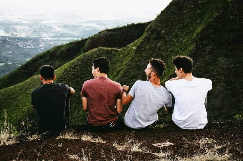 des amis masculins assis sur la colline