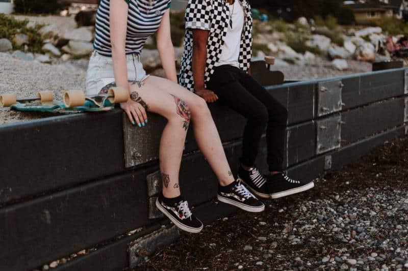 deux personnes s'assoient sur une barrière