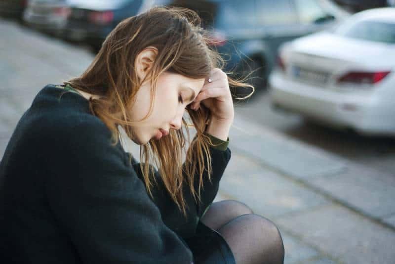 femme épuisée, assise dans la rue, dehors