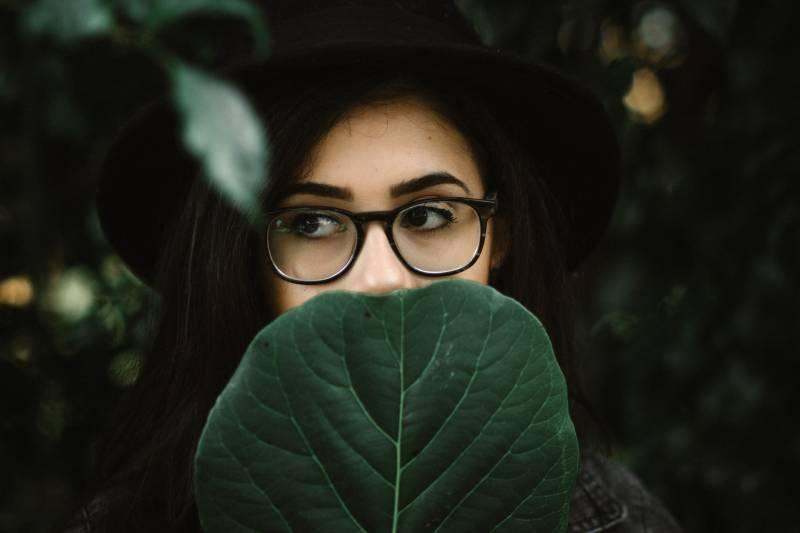 femme couvrant sa bouche de feuilles vertes