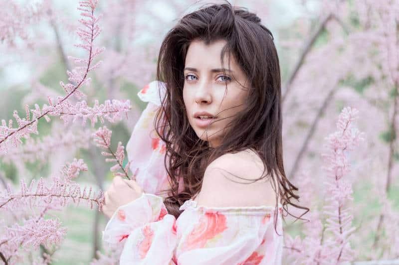 femme debout près d'un champ de feuilles roses