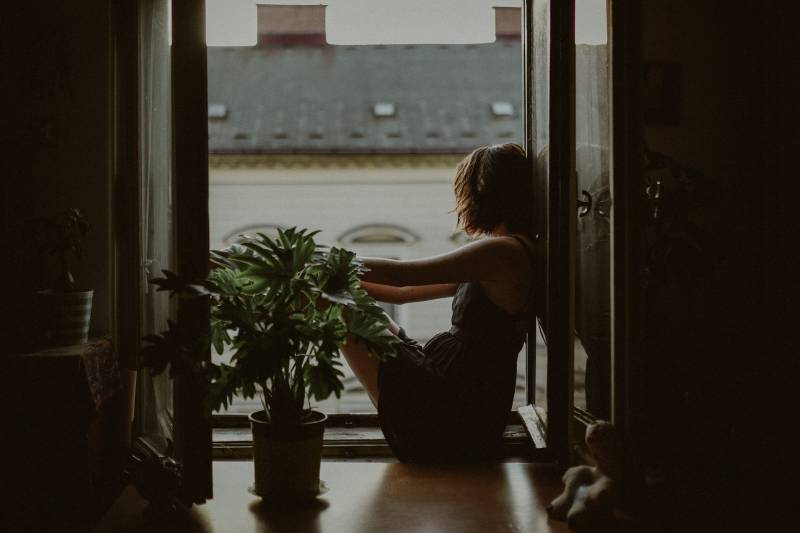 femme debout sur la porte, regardant dehors