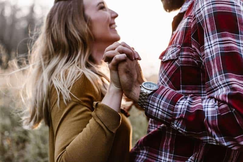femme devant un homme se tenant par la main