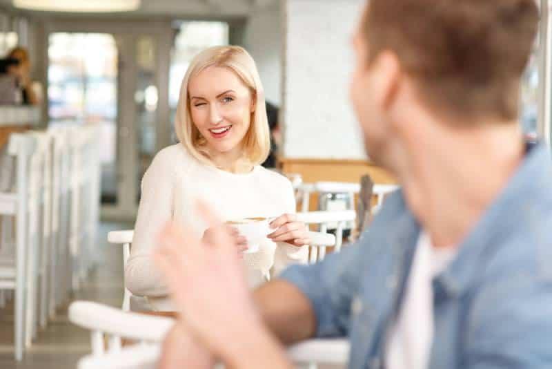 femme flirtant avec un homme dans un café