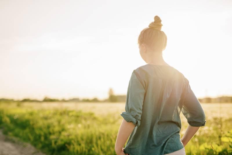 femme marchant près d'un champ d'herbe