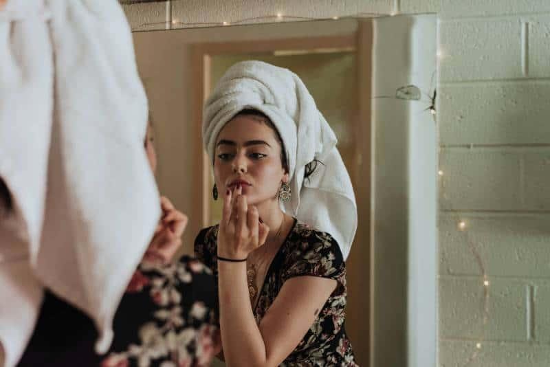 femme se maquillant devant le miroir
