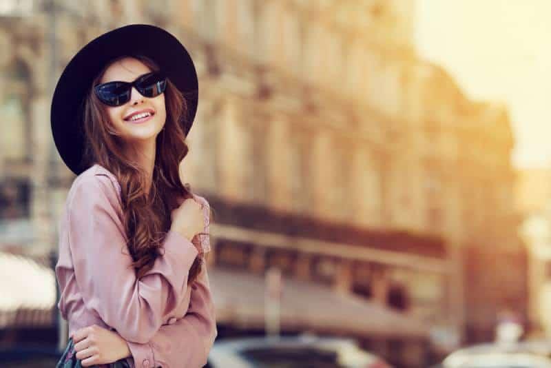 femme souriante portant un chapeau noir et des lunettes de soleil