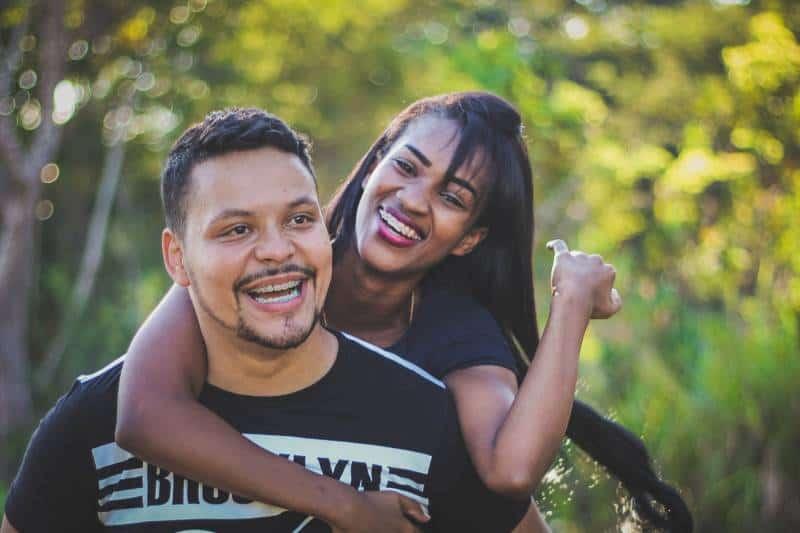 femme sur le dos de son homme souriant