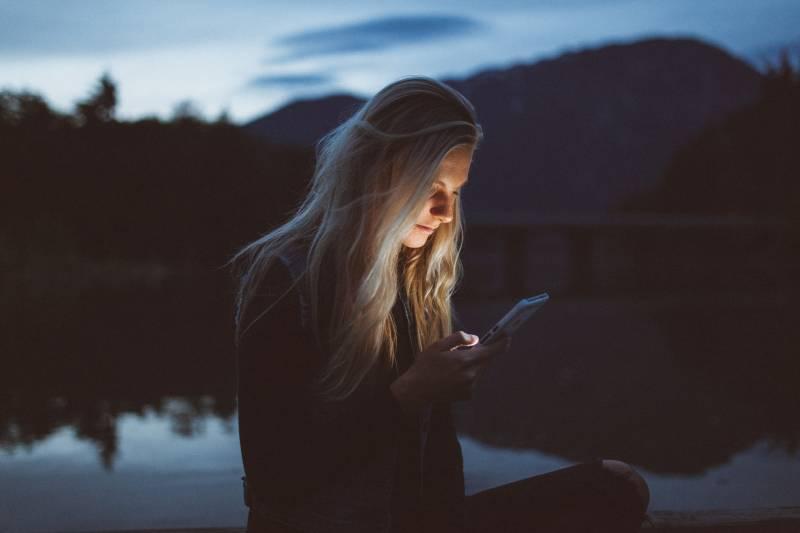 femme tapant un sms le soir au bord du lac