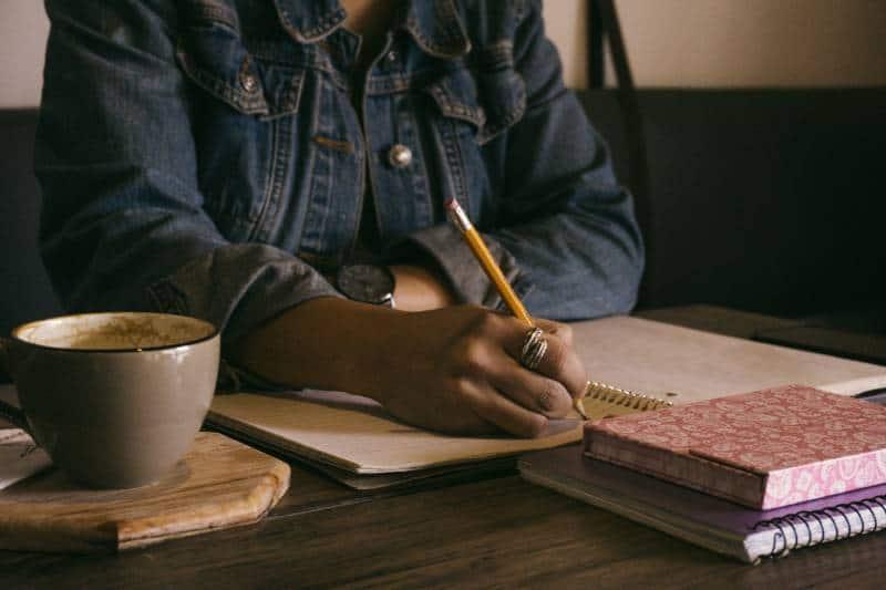 fille écrivant dans un carnet à la maison