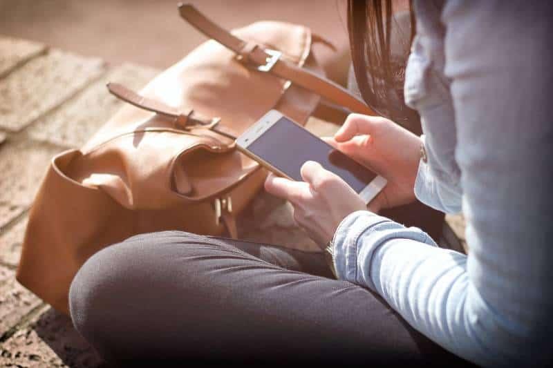 fille assise sur des briques et tapant un sms