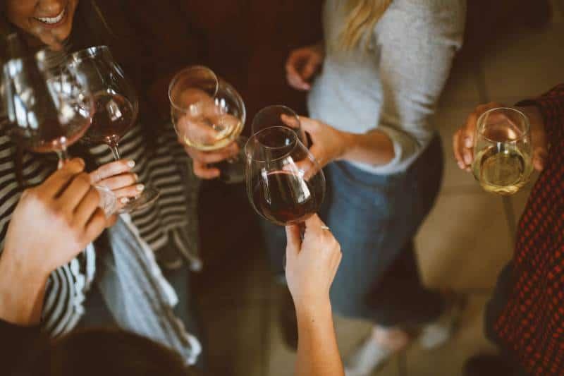 groupe d'amis acclamant avec des verres de vin