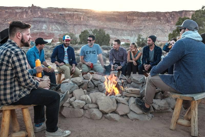 groupe d'amis assis autour d'un feu et discutant