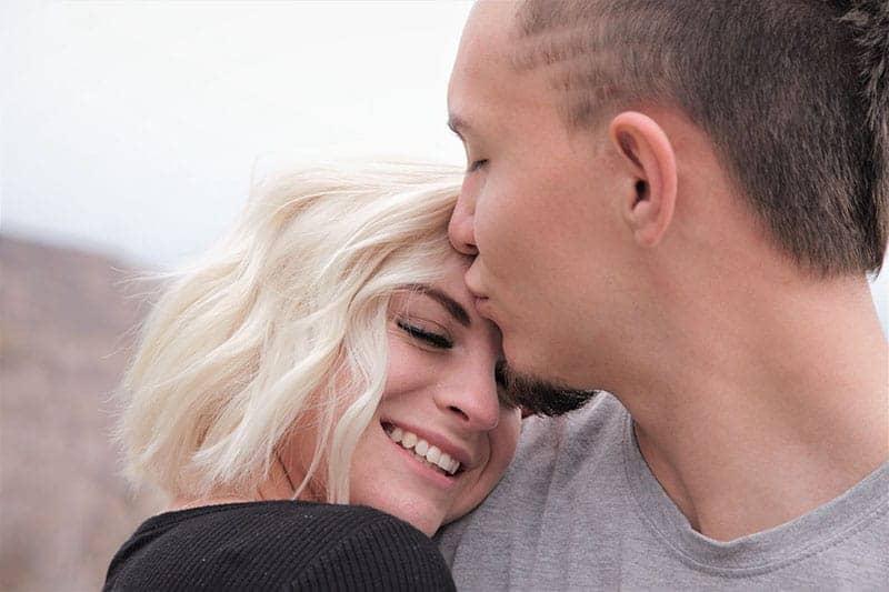 homme embrassant sa petite amie souriante sur le front