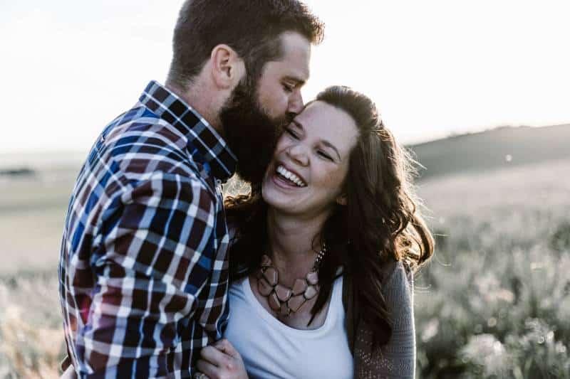 homme embrassant sa petite amie sur la joue à l'extérieur